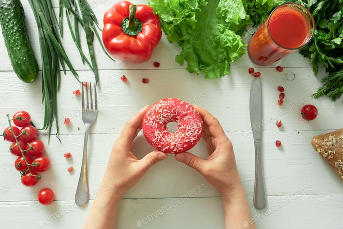 Female hands hold a tasty donut on a background of vegetables. The temptation of dieting