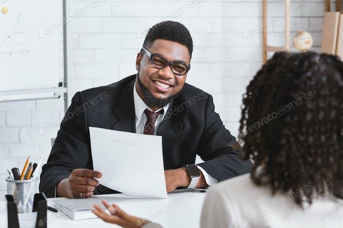 Glücklicher Personalmanager und junger Bewerber im Arbeitsgespräch im Firmenbüro