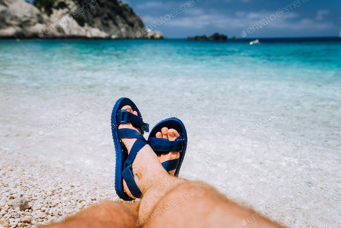 Young male crossed feets in blue flip-flop sandal sunbathing on sea beach