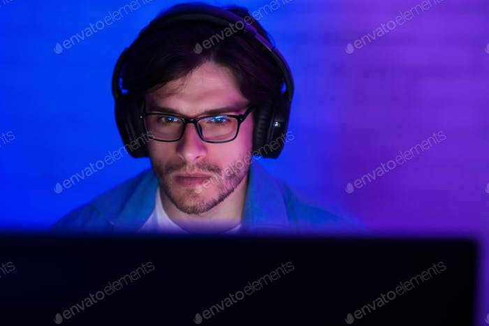 Young man in headset playing game at home