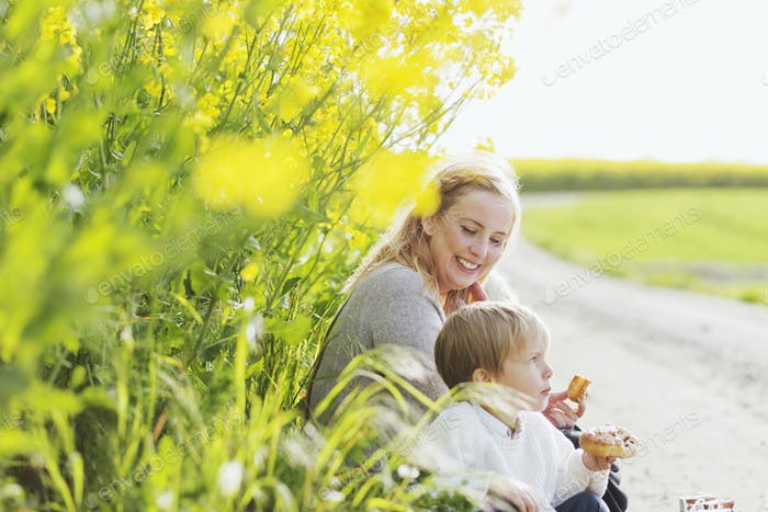 Happy woman looking at boy holding bread while sitting at oilseed rape field