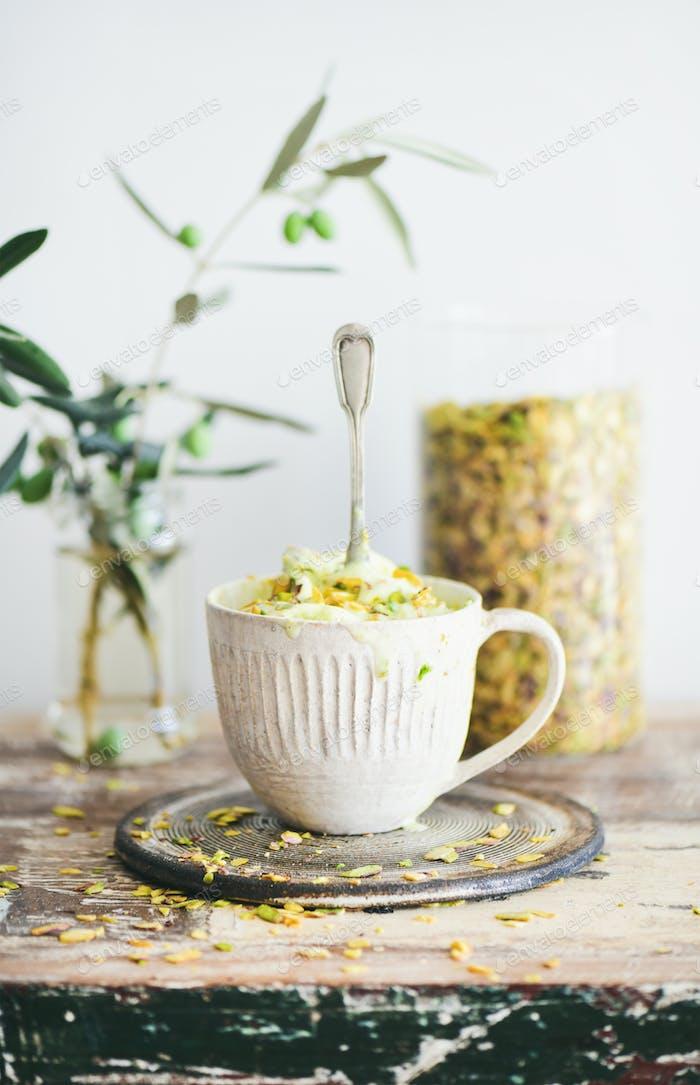 Pistachio ice cream with pistachio nuts in mug, selective focus