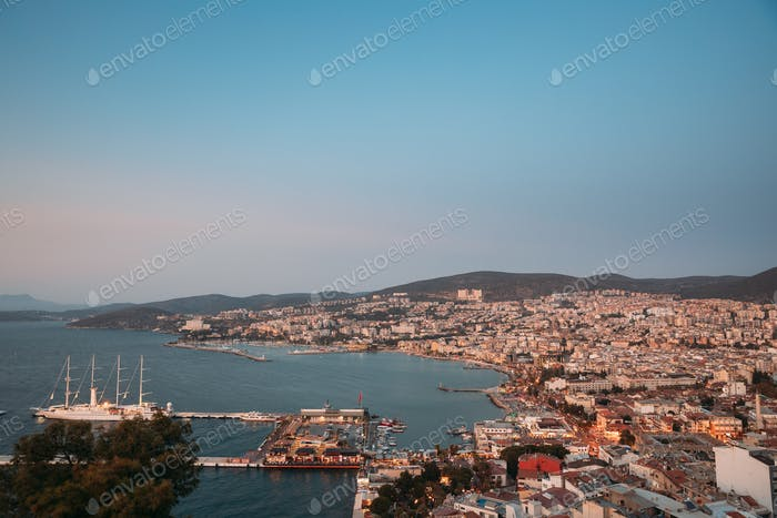 Kusadasi, Aydin Province, Turkey. Waterfront And Kusadasi Cityscape In Summer Evening. Scenic View