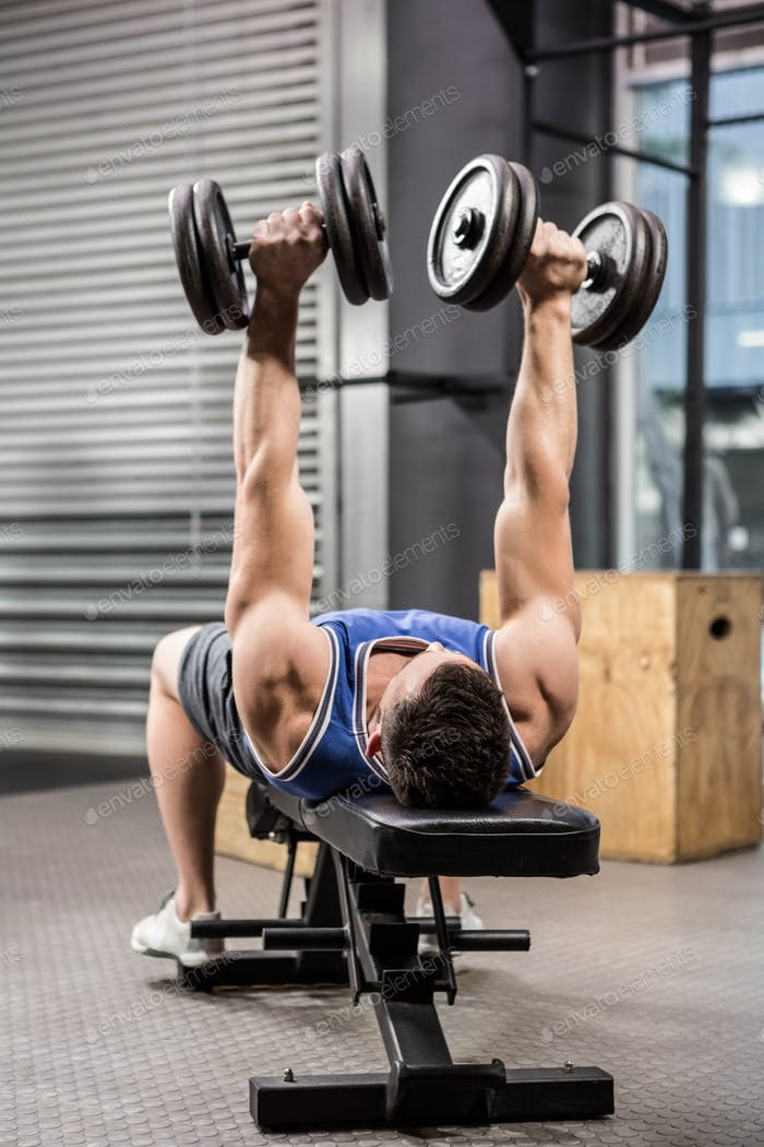 Muscular man on bench lifting dumbbells at the crossfit gym