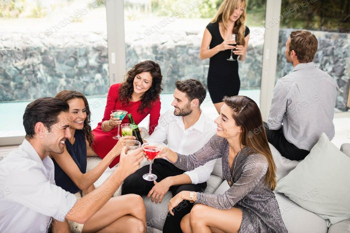 Group of friends toasting cocktail drinks and enjoying party