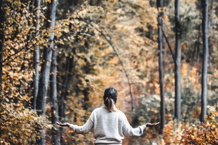 Autumn girl standing backwards and watching nature. Autumn forest colors with girl back view