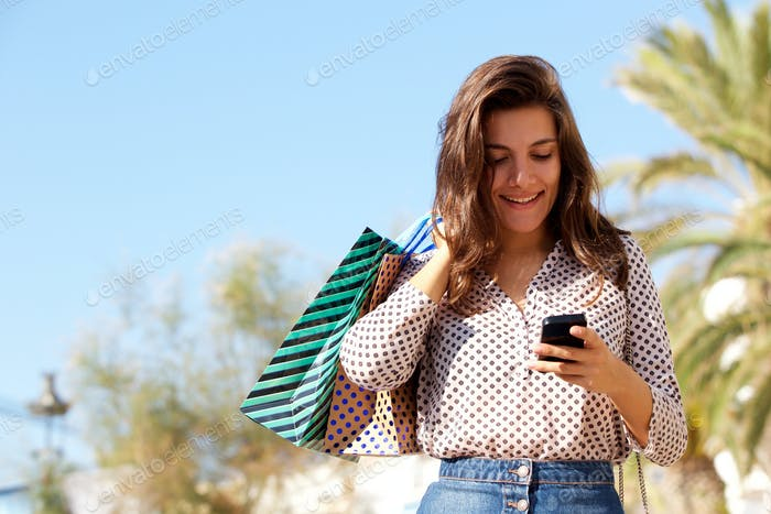 Happy woman standing with gift bags on mobile phone