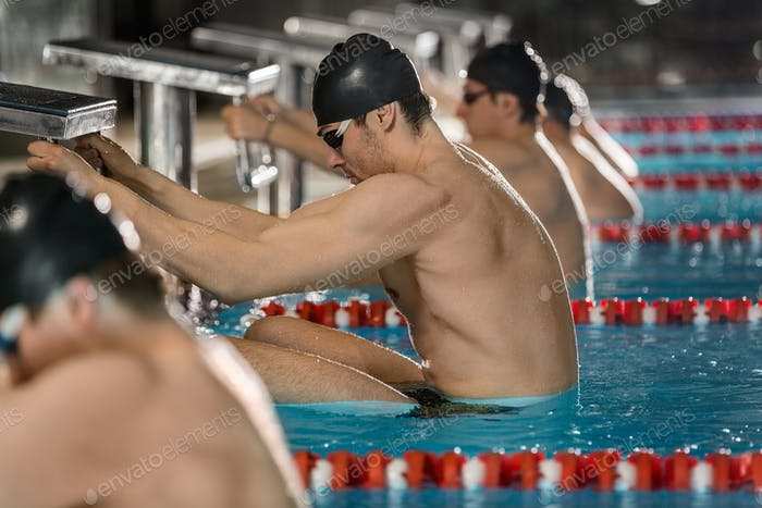 Male swimmers holding their starting blocks