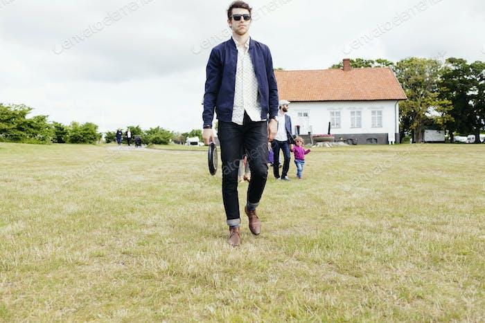 Full length of family walking on grassy field