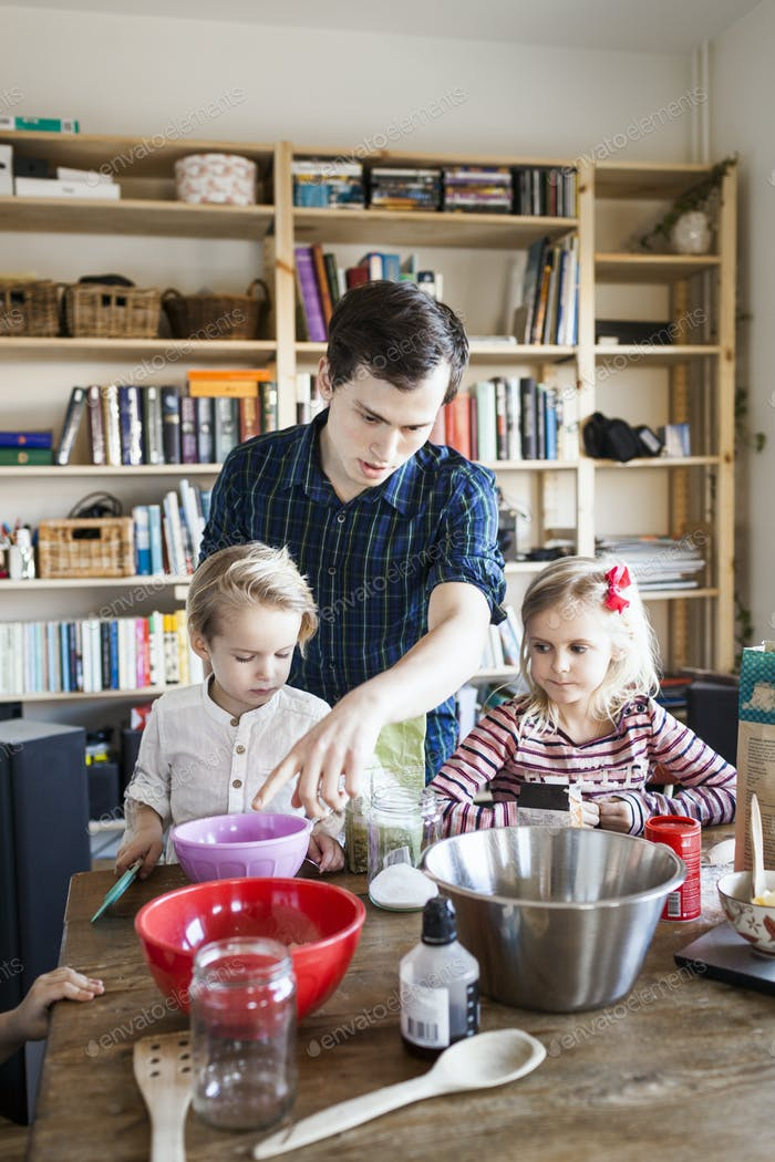 Young man guiding children in baking at home