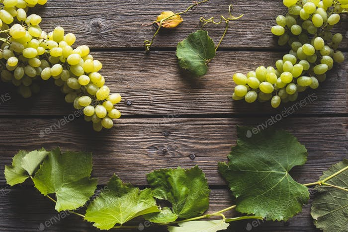 fresh Green grape with leaves on wooden background