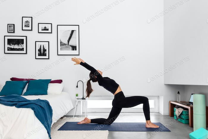 Fit woman practicing Half Moon pose at home