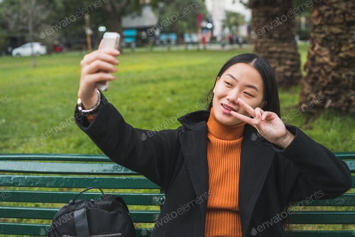 Asian woman taking selfie with phone.
