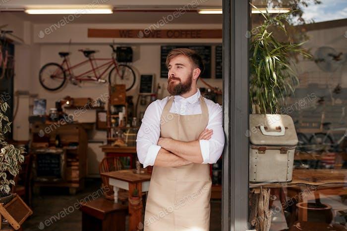 Cafe owner standing in the doorway of his coffee shop
