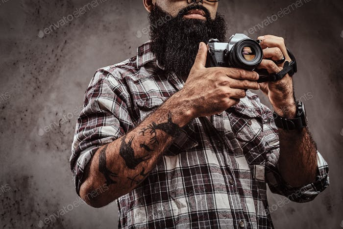 Cropped image of a tattooed bearded male wearing a checkered shirt holding a camera.