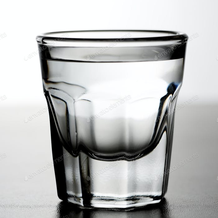 Shot glass of alcoholic drink as tequila or vodka or gin