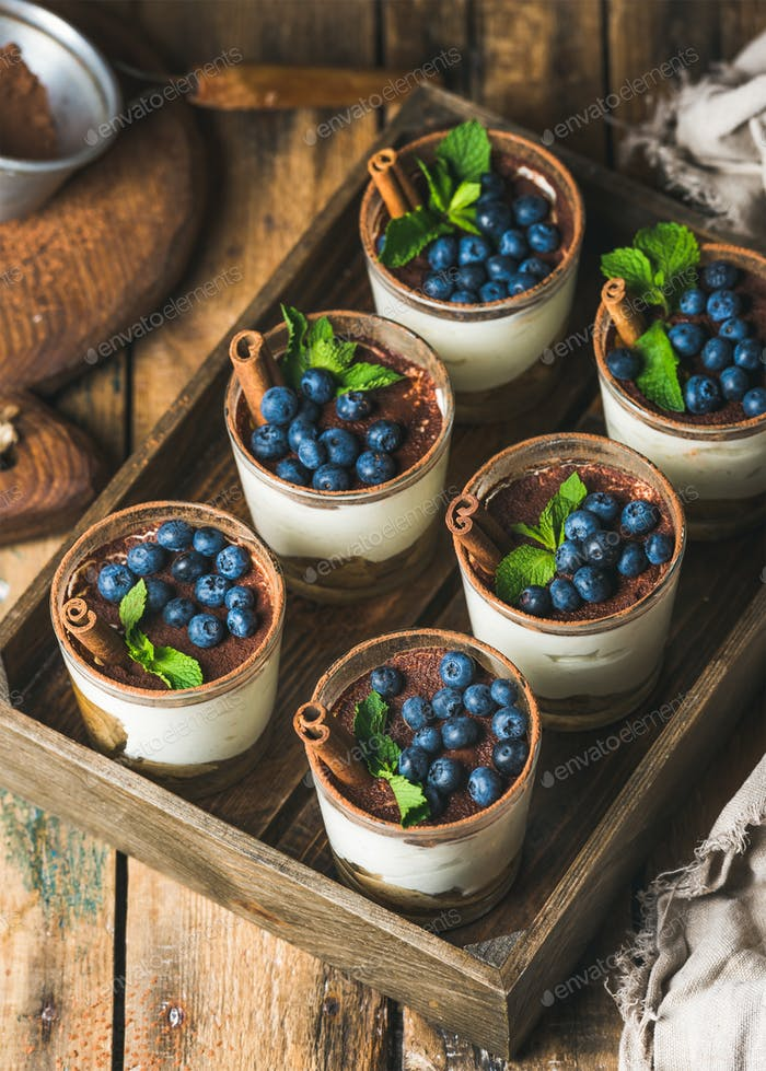 Tiramisu dessert with cinnamon, mint and blueberry in wooden tray