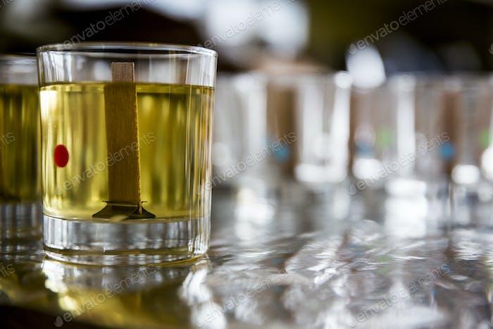 Nahaufnahme der handgefertigten Glaskerze mit flüssigem Wachs und Holzdocht.
