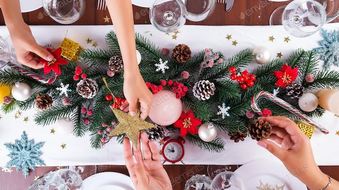 Christmas table setting with christmas decoration, mom and child hands handing stars on dark wooden