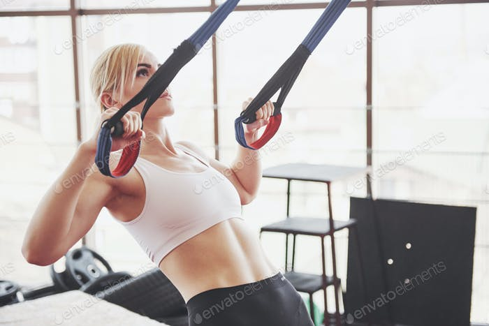 Women doing push ups training arms with trx fitness straps in the gym Concept workout healthy