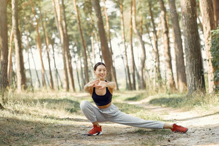 Beautiful woman training in a summer park