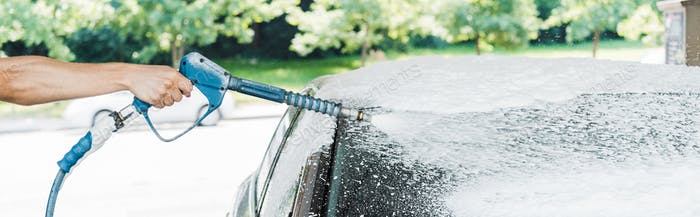 panoramic shot of man holding pressure washer with foam near car