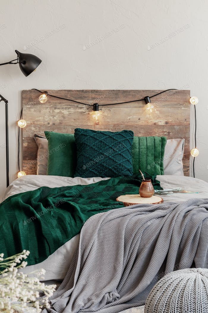 Emerald green pillows and blanket on wooden king size bed with grey bedding