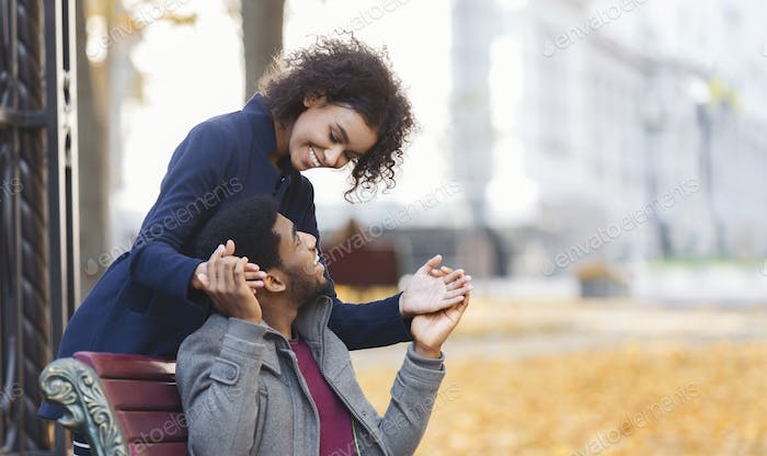 Pretty afro couple playing together at autumn park