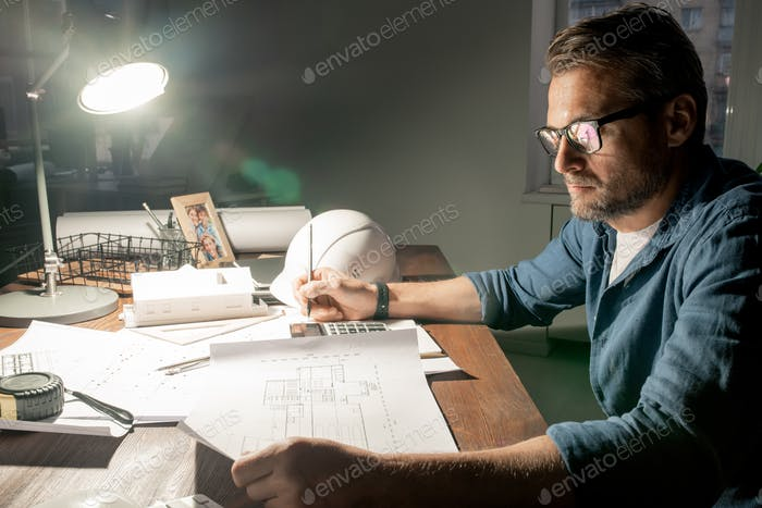 Serious engineer decided to stay at work for night to check sketches