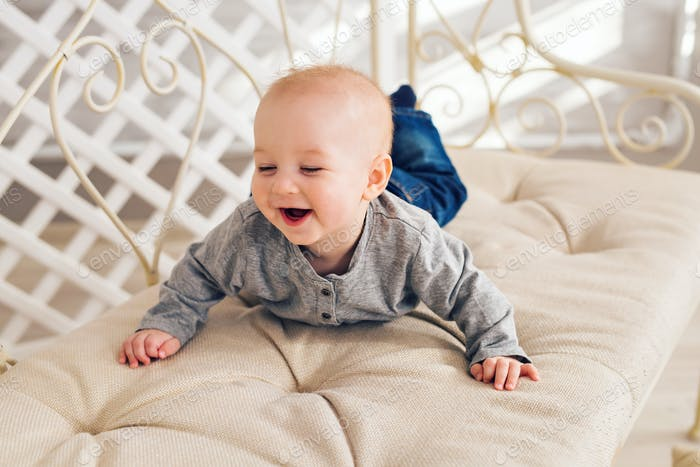 Adorable baby boy in sunny bedroom. Newborn child
