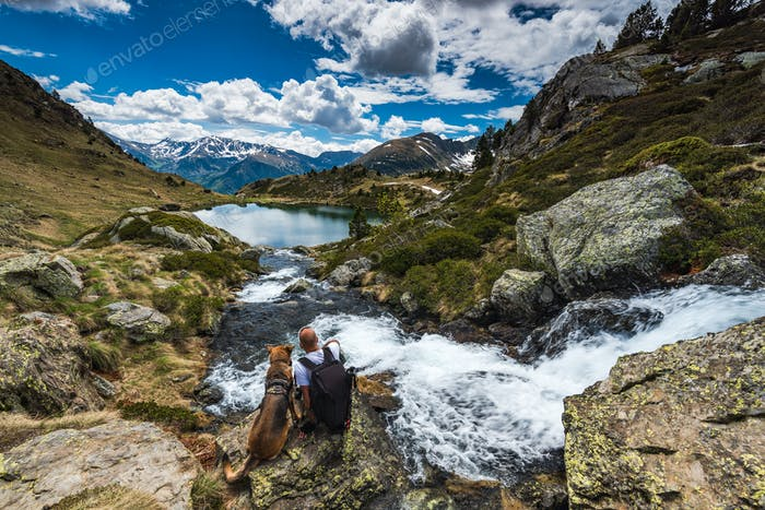 Active man sit on rock with dog while trekking