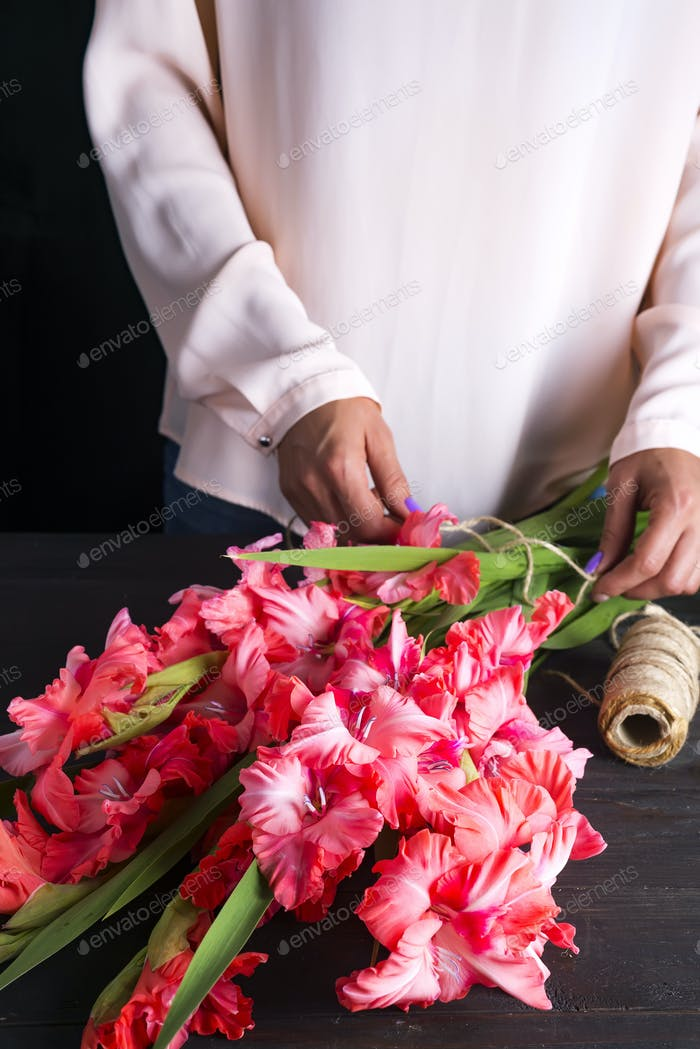 women's hands create a bouquet of flowers of gladiolus