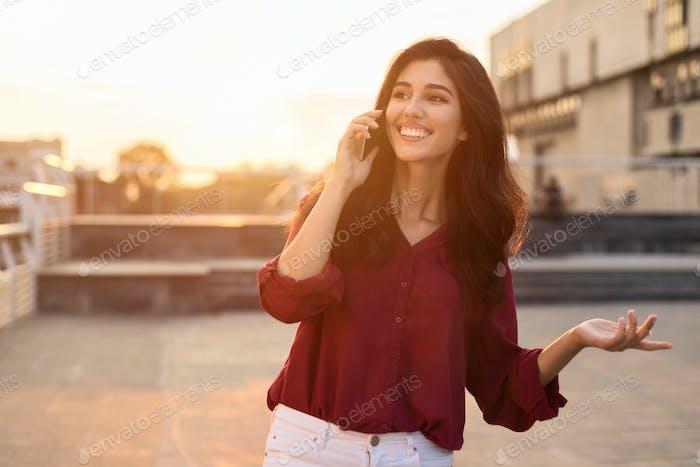 Beautiful woman having phone talk outdoors, walking in city