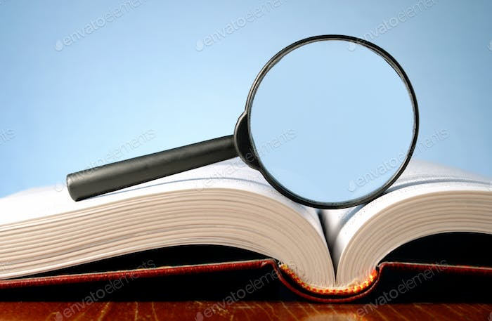 book and a magnifying glass on a blue background