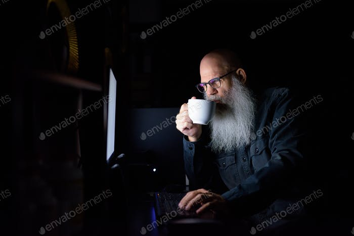 Mature bald bearded man drinking coffee while working overtime at home in the dark