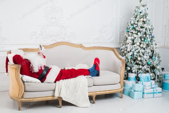 Santa Claus ruht auf einem Sofa zu Hause.