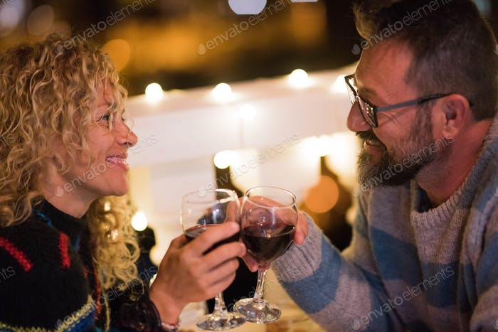 romantic couple of two adults celebrating their anniversary together eating and drinking wine