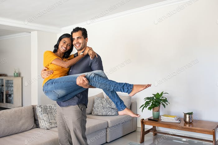 Latin man in love carrying beautiful woman at home
