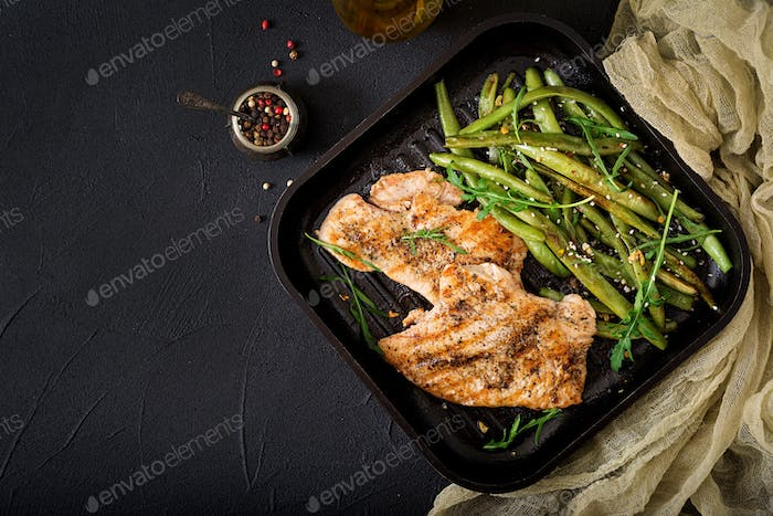 Turkey- chicken fillet cooked on a grill and garnish of green beans. Flat lay. Top view