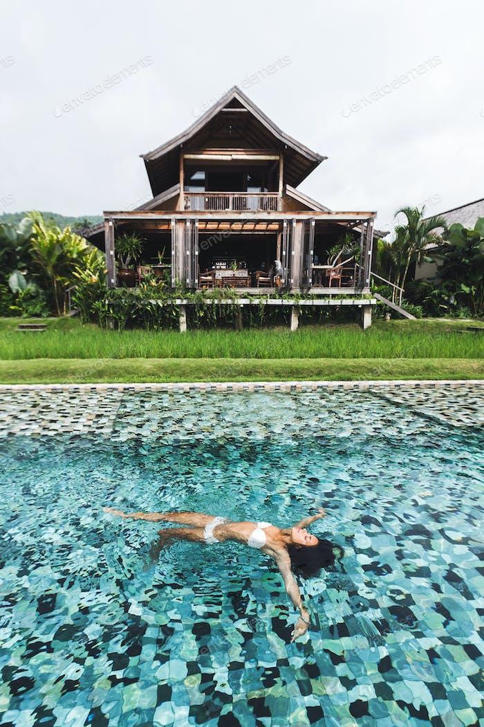 Frau entspannt sich im Luxusschwimmbad im weißen Bikini