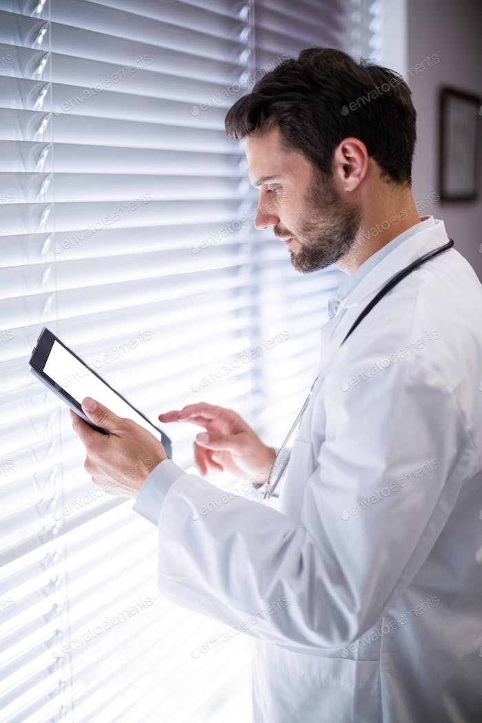Male doctor using digital tablet
