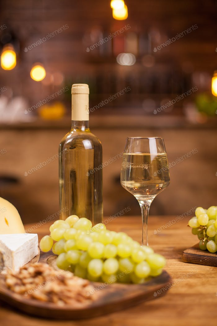 Bottle of white wine a glass full of it next to different cheeses