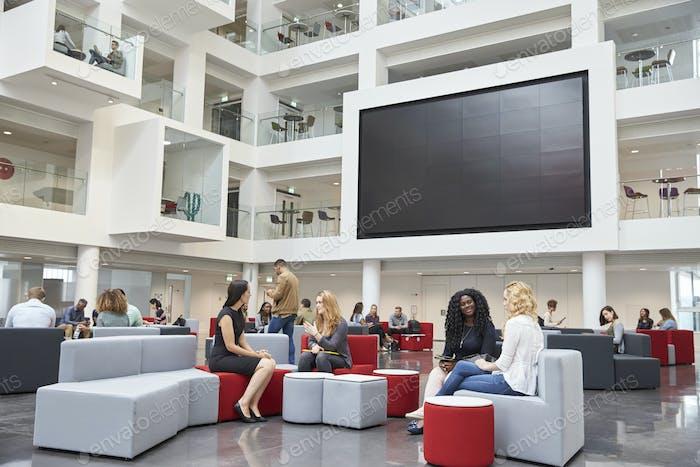 Students sit talking under AV screen in atrium at university