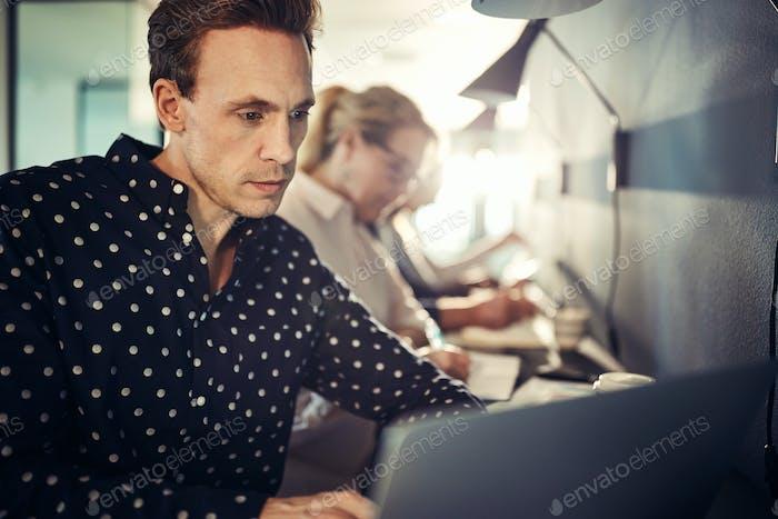 Fokussierte junge Designer sitzen mit Kollegen mit einem Laptop