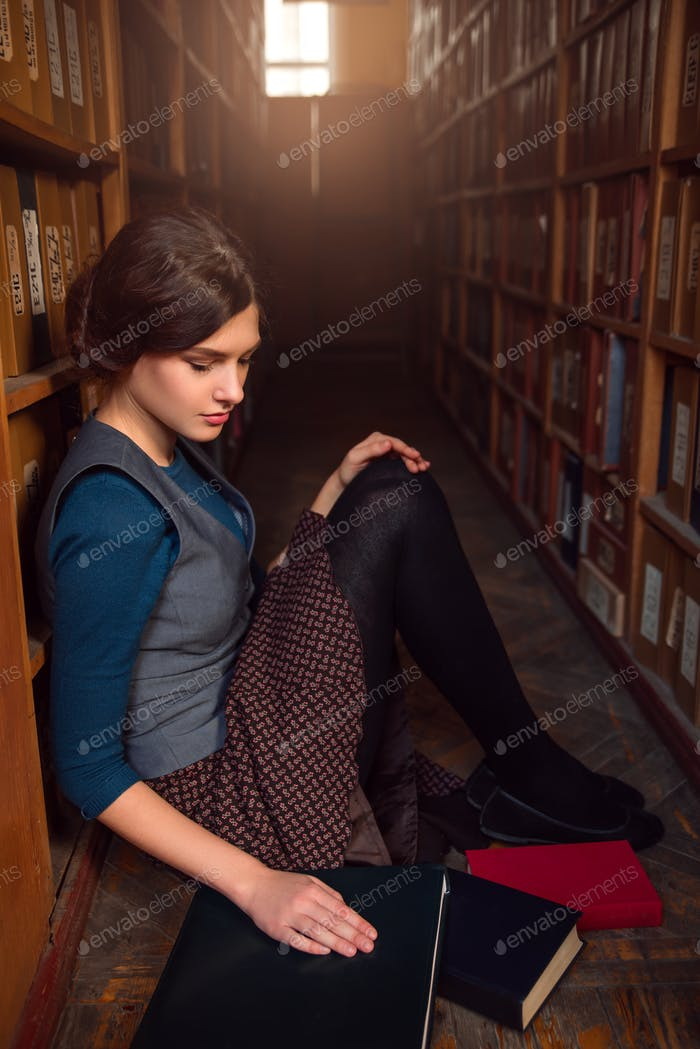 University student sitting on a floor of library.
