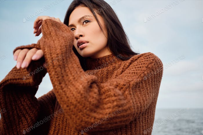 Beautiful Asian brunette girl in cozy knitted sweater dreamily looking away posing on seaside