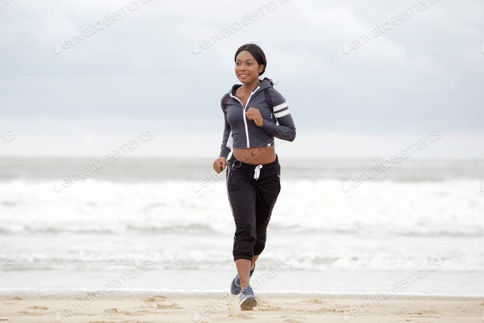 Full body sporty young black woman running on beach by water