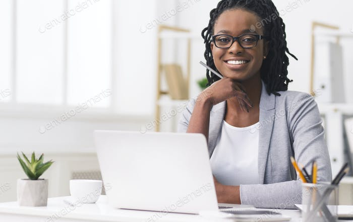 Confident African American Businesswoman Smiling At Camera At Workplace