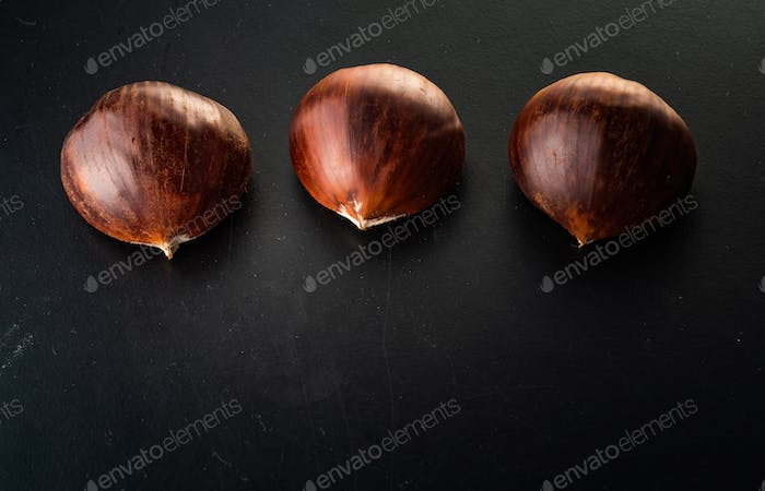 Three chestnuts isolated on black background