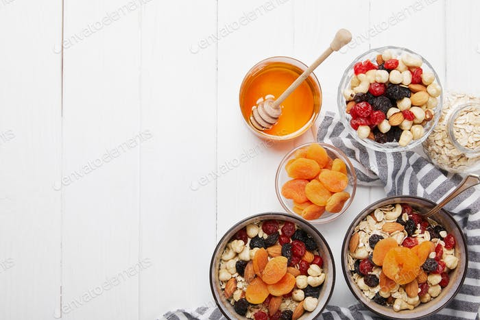 top view of bowls with muesli, dried berries and nuts served for breakfast with dried apricots and